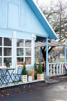 Houten tafel en stoelen op veranda van huis.