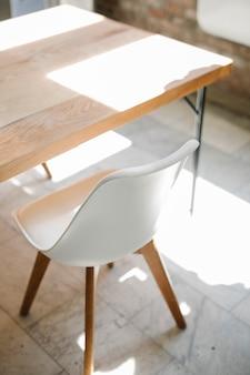 Houten tafel en witte stoel op een marmeren vloer