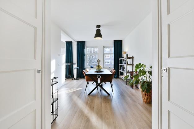 Houten tafel en zachte stoelen in ruime eetkamer in modern appartement verlicht door zonlicht