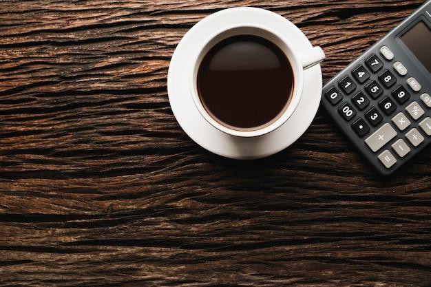 Houten tafel houten bureau met koffie en rekenmachine. bovenaanzicht van koffiekopje op houten achtergrond met kopie ruimte.