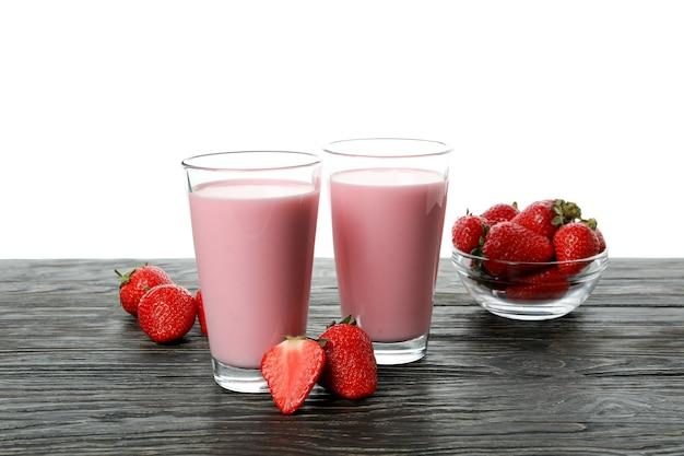 Houten tafel met aardbeienmilkshakes en ingrediënten, geïsoleerd op een witte achtergrond
