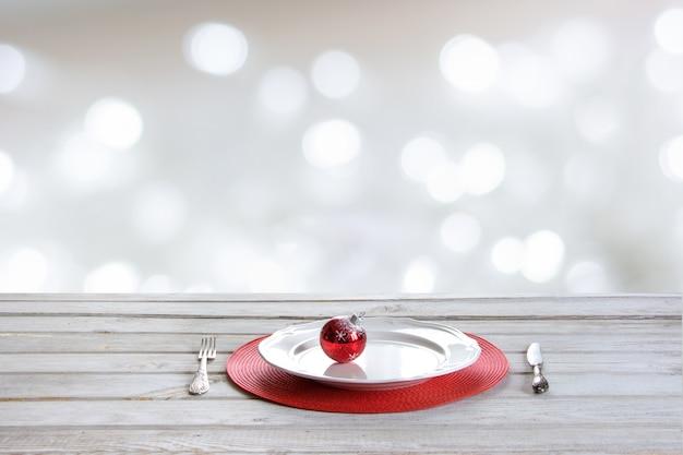 Houten tafel met bestek, bord en kerstbal