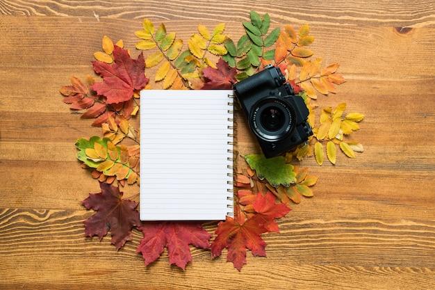 Houten tafel met blanco vel voorbeeldenboek omgeven door kleurrijke herfstbladeren met fotocamera in de buurt
