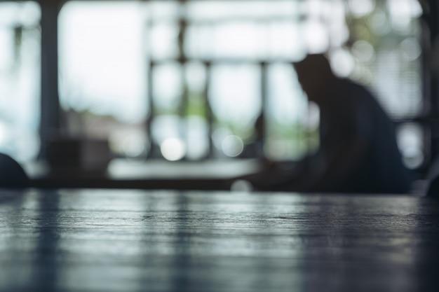 Houten tafel met donkere vervagen bokeh abstracte achtergrond in café
