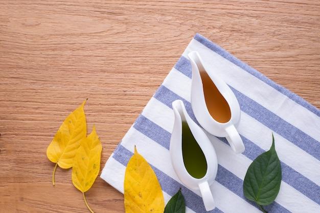 Houten tafel met een kopje sap en blad. bovenaanzicht.