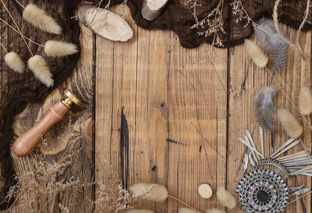Houten tafel met gedroogde planten en boheemse decoraties met kopieerruimte, bovenaanzicht
