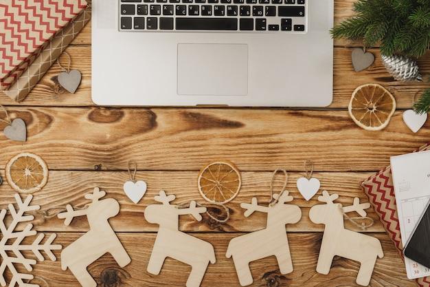 Houten tafel met kantoorapparatuur en kantoorbehoeften omringd met nieuw jaar feestelijk decor, mening van hierboven