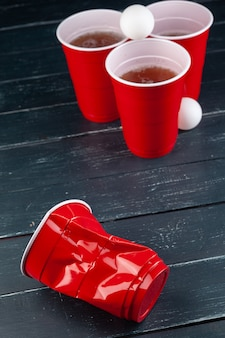 Houten tafel met rode bekers en bal voor bierpong