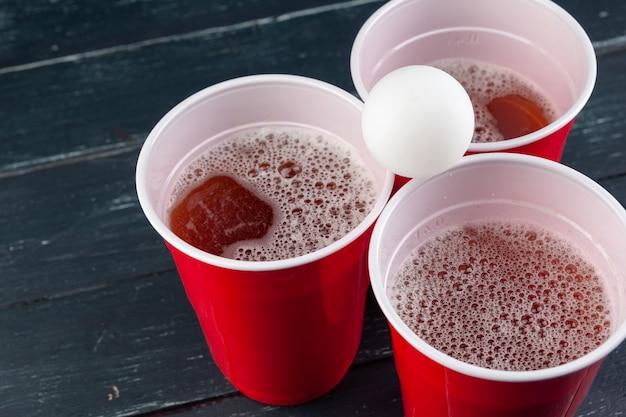 Houten tafel met rode kopjes en bal voor bier pong