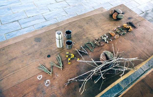 Houten tafel met thermoskan, koffiekopjes en reislustwoord gemaakt met natuurlijke voorwerpen
