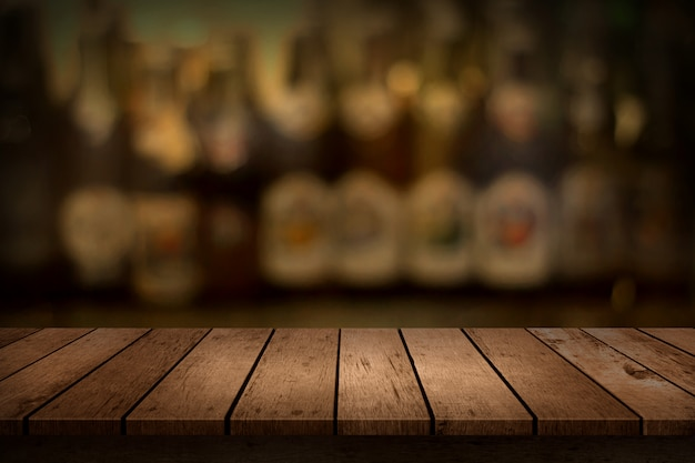 Houten tafel met uitzicht op wazig dranken bar fles achtergrond.