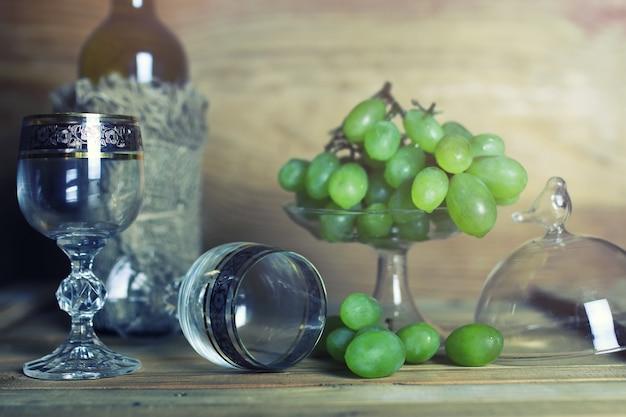 Houten tafel met wijnflesboek en druif