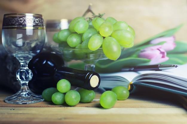 Houten tafel met wijnflessenboek en druif