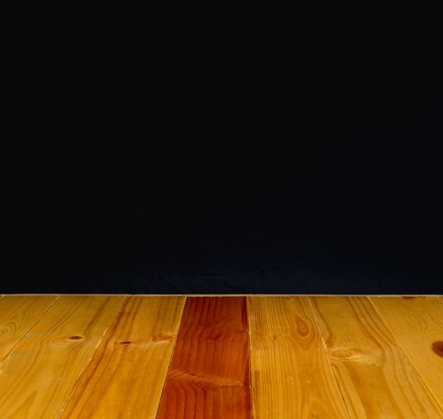 Houten tafel of bureau met zwarte muur achtergrond.