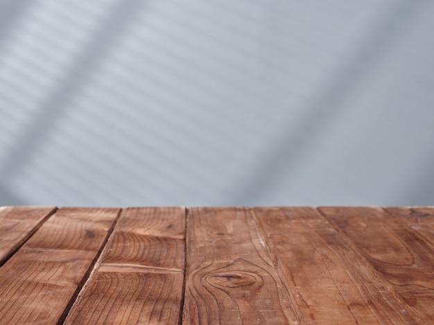 Houten tafel op de achtergrond van een betonnen muur met licht uit het raam