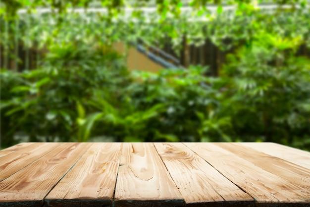 Houten tafel op de achtergrond van groene planten in de tuin in de middag