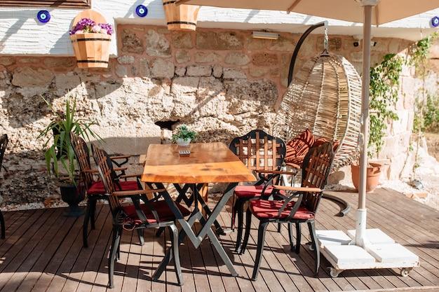 Houten tafel op het terras onder een parasol in de openluchtstad side, turkije. mooi meubilair in de buurt van de oude muur op straat.