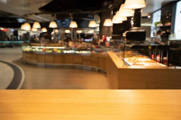 Houten tafel op onscherpe achtergrond van moderne restaurantruimte of coffeeshop voor productvertoning mockup
