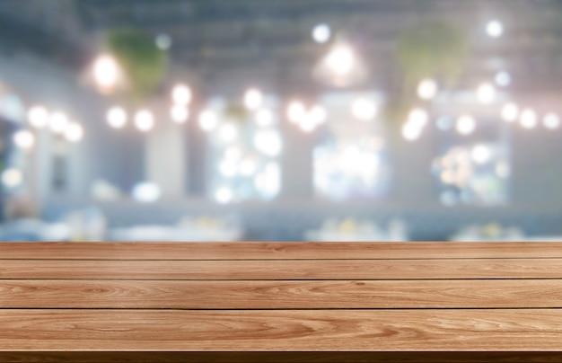 Houten tafel op onscherpe achtergrond van moderne restaurantruimte of coffeeshop voor productvertoning mockup.