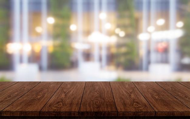 Houten tafel op onscherpe achtergrond van moderne restaurantruimte of koffieshop voor productvertoning