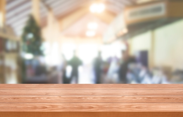 Houten tafel op onscherpe achtergrond van moderne restaurantruimte of koffieshop voor productweergave