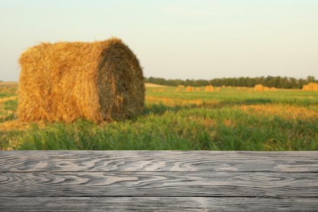 Houten tafel tegen veld met stro broodjes. landbouw concept. mockup