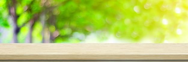 Houten tafel, tegenachtergrond, houten plank en vervagen groene boomaard voor productvertoning