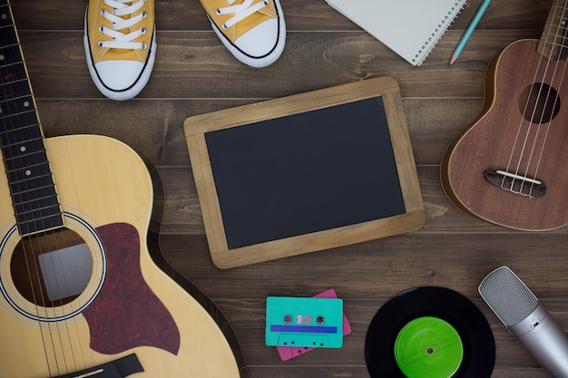 Houten tafel van muziekcomponist, gitaar, ukelele, notitieboekje, audiocassettes, microfoon, bandrecorder
