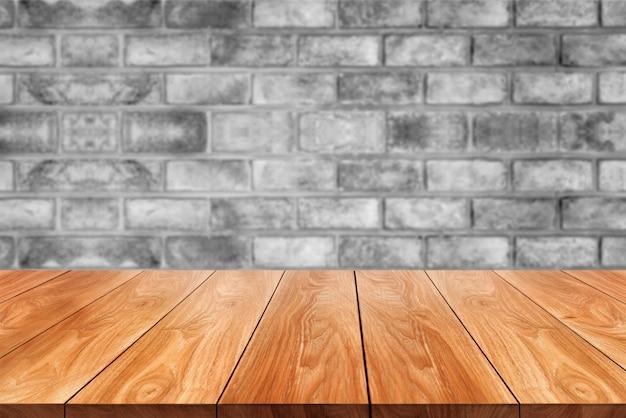 Houten tafel voor rustieke bakstenen muur achtergrond met lege kopie ruimte op de tafel wazig.
