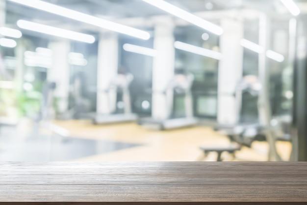 Houten tafelblad achtergrond op wazig fitness gym