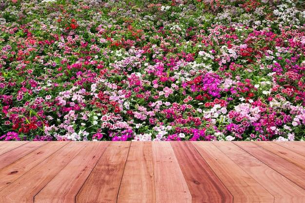Houten tafelblad en roze bloem achtergrond.