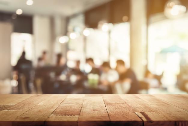 Houten tafelblad met vervagen café interieur en mensen op de achtergrond