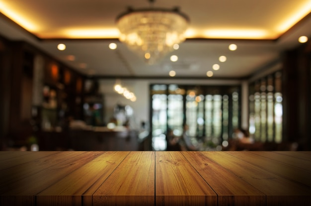 Houten tafelblad met vervagen coffeeshop of restaurant interieur achtergrond