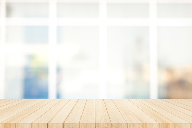 Houten tafelblad met vervagen glas venster muur achtergrond.