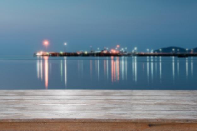 Houten tafelblad met wazig zee zonsondergang achtergrond, retro filtereffect