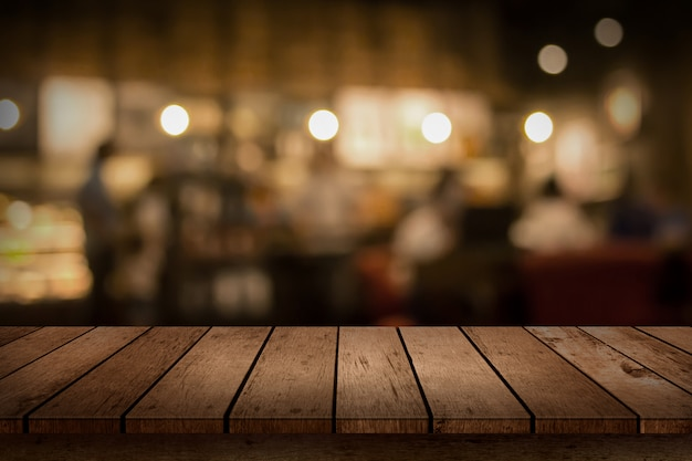 Houten tafelblad op bokeh coffeeshop of café restaurant achtergrond.
