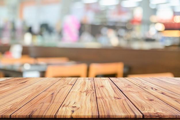 Houten tafelblad op onscherpe achtergrond van interieur coffeeshop of restaurant vervagen café coffeeshop achtergrond