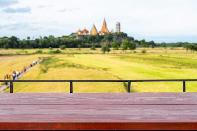Houten tafelblad op terras met gouden pagode met rijstveld