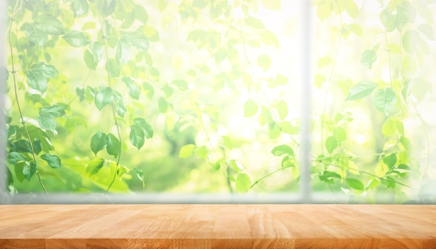 Houten tafelblad op vervaging van venster met tuin bloem achtergrond in de ochtend