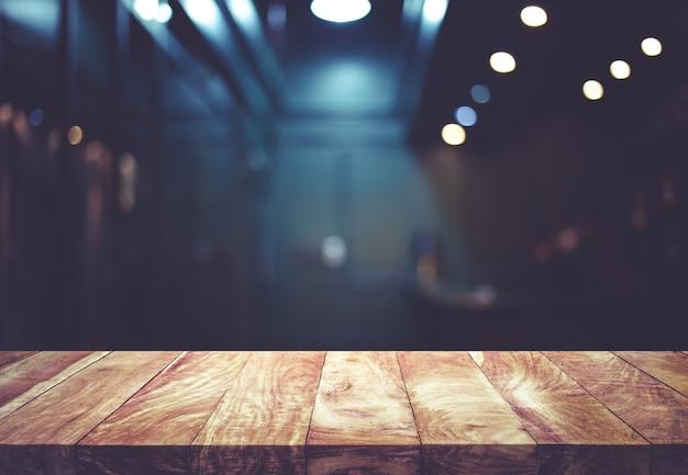 Houten tafelblad op wazig van teller café winkel met gloeilamp achtergrond