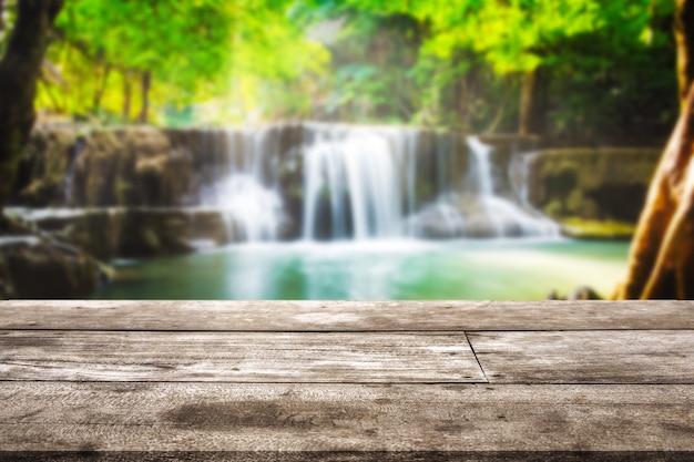 Houten tafelblad op wazige waterval in tropisch regenwoud bij huai mae khamin background