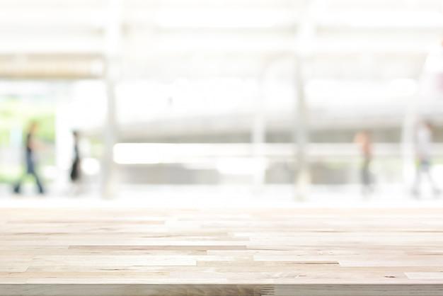 Houten tafelblad op witte vervagen abstracte achtergrond van buiten overdekte loopbrug in de stad