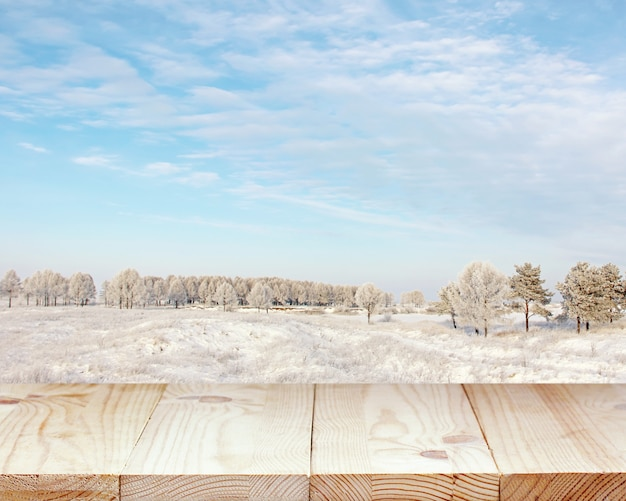 Houten tafelblad tegen de achtergrond van een winterlandschap.