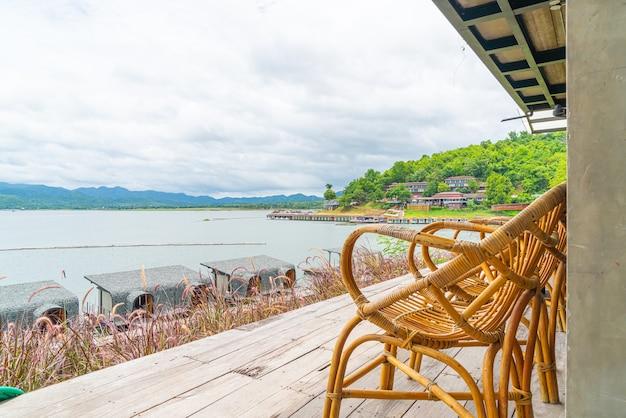 Houten tafels en stoelen in een restaurant aan een meer