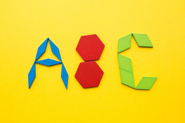 Houten tangrampuzzel in alfabet abc-brievenvorm op gele achtergrond