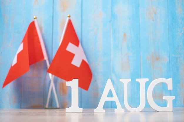 Houten tekst van 1 augustus met miniatuur zwitserland vlaggen. nationale feestdag van zwitserland en gelukkige vieringsconcepten