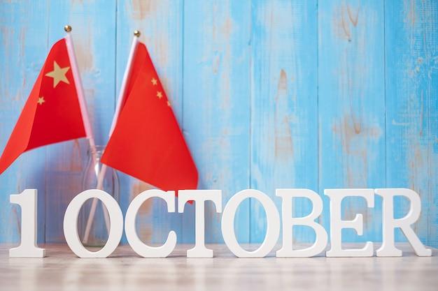 Houten tekst van 1 oktober met vlaggen van china. nationale feestdag van de volksrepubliek china, nationale feestdag en gelukkige vieringsconcepten