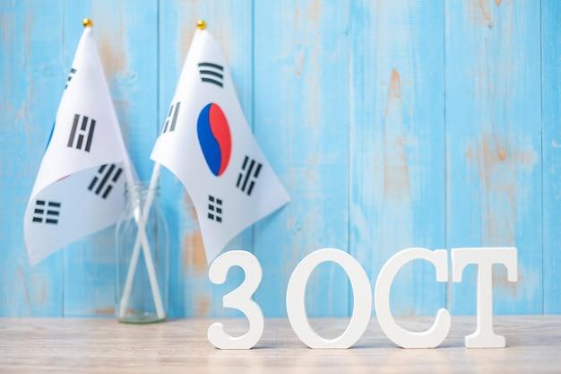Houten tekst van 3 oktober met vlaggen van de republiek korea. nationale stichtingsdag, gaecheonjeol, nationale feestdag en gelukkige vieringsconcepten