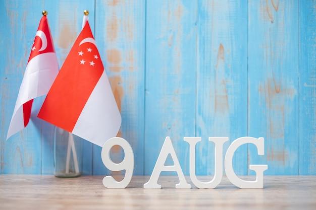 Houten tekst van 9 augustus met miniatuur singaporese vlaggen. de onafhankelijkheidsdag van singapore, de nationale feestdag van de stadstaat en de concepten van de gelukkige vieringsrepubliek