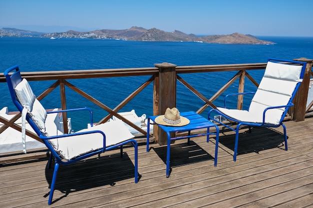 Houten terras van vakantievilla met twee witte stoelen